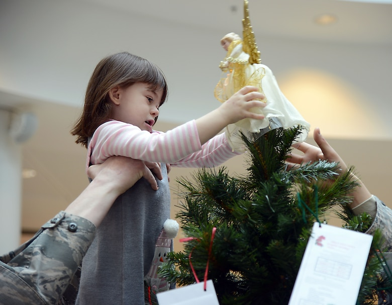 Master Sgt. Timothy Bliefnick, 86th Comptroller Squadron and Wing Staff Agencies first sergeant, helps his daughter, Annabella, place an angel decoration on top of a tree in the Kaiserslautern Military Community Center at Ramstein Air Base, Germany, Nov. 17, 2014. Thirteen trees are set up around the Kaiserslautern Military Community area to accept donations, meant to be used to provide financial relief to military families during the holiday season. (U.S. Air Force photo/Senior Airman Timothy Moore)