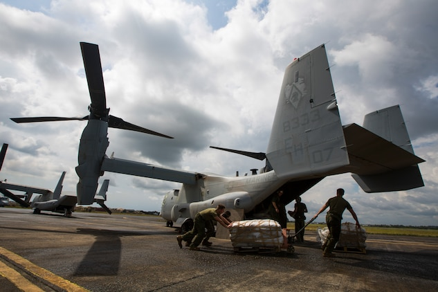 U.S. Marines and Sailors with SPMAGTF Crisis Response - Africa prepare to load bags of concrete onto an MV-22B Osprey to help local and international health organizations build Ebola Treatment Units while in support of Operation United Assistance in Monrovia, Liberia, Nov. 21, 2014. United Assistance is a Department of Defense operation to provide command and control, logistics, training, and engineering support to U.S. Agency for International Development- led efforts to contain the Ebola virus outbreak in West African nations. (U.S. Marine Corps photo by Lance Cpl. Andre Dakis/SPMAGTF-CR-AF Combat Camera/Released)