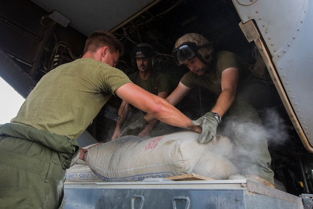 U.S. Marines with SPMAGTF Crisis Response - Africa load bags of concrete, that will be used by local and international health organizations to build Ebola Treatment Units, into an MV-22B Osprey during Operation United Assistance in Monrovia, Liberia, Nov. 21, 2014. United Assistance is a Department of Defense operation to provide command and control, logistics, training, and engineering support to U.S. Agency for International Development- led efforts to contain the Ebola virus outbreak in West African nations. (U.S. Marine Corps photo by Lance Cpl. Andre Dakis/ SPMAGTF-CR-AF Combat Camera/Released)