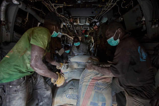 U.S. Navy Lt. Jeffery Fornadley, a flight surgeon with SPMAGTF Crisis Response – Africa, helps members of Samaritan's Purse, an international relief group, offload, from an MV-22B Osprey, bags of concrete that will be used to by health organizations to build Ebola Treatment Units, while in support of Operation United Assistance in Fish Town, Liberia, Nov. 21, 2014. United Assistance is a Department of Defense operation to provide command and control, logistics, training, and engineering support to U.S. Agency for International Development- led efforts to contain the Ebola virus outbreak in West African nations. (U.S. Marine Corps photo by Lance Cpl. Andre Dakis/SPMAGTF-CR-AF Combat Camera/Released)