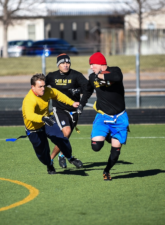 Soldiers from the 743rd Military Intelligence Battalion scramble on the field during their 2nd Annual Turkey Bowl football game Nov. 26, 2014 at the multipurpose field on Buckley Air Force Base, Colo. The officers challenged the NCOs during their pre-Thanksgiving game. (U.S. Air Force photo by Senior Airman Riley Johnson/Released)