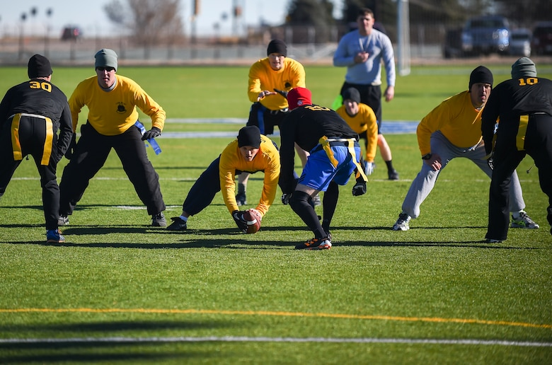 Soldiers from the 743rd Military Intelligence Battalion move into position during their 2nd Annual Turkey Bowl football game Nov. 26, 2014 at the multipurpose field on Buckley Air Force Base, Colo. The officers challenged the NCOs during their pre-Thanksgiving game. (U.S. Air Force photo by Senior Airman Riley Johnson/Released)