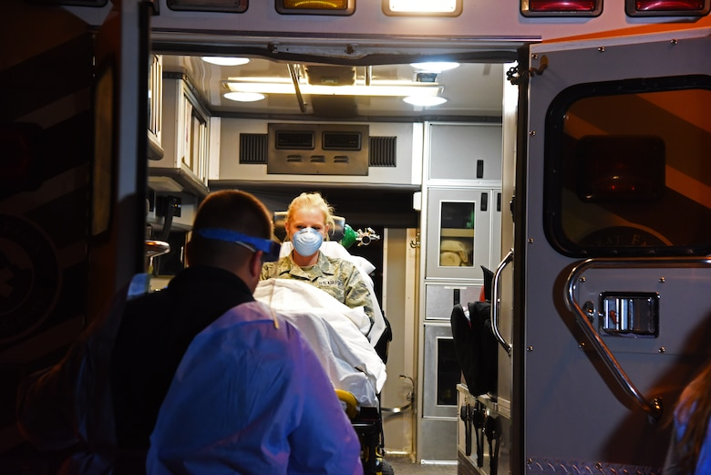 Airman 1st Class Kaitlyn Arteaga, 341st Medical Operations Squadron physical therapy technician, is loaded into the back of an ambulance by a Benefis Health System emergency responder during an Ebola exercise at the Malmstrom Air Force Base Clinic Nov. 25. The exercise was performed in conjunction with Great Falls Emergency Services, Great Falls Fire/Rescue, the Great Falls Clinic, Benefis Health System and the Cascade City-County Health Department. (U.S. Air Force photo/Airman 1st Class Collin Schmidt)