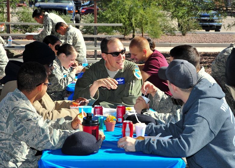 U.S. Air Force Col. James P. Meger, 355th Fighter Wing commander, talks with Airmen during a Thanksgiving Dorm Bash held at Davis-Monthan Air Force Base, Ariz., Nov. 25, 2014.  This event was hosted by dorm management and the Chapel to allow dorm residents the opportunity to eat a home-cooked meal and to celebrate the holiday with each other. (U.S. Air Force Photo by Airman 1st Class Chris Massey/Released)
