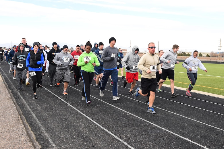Team Buckley members take off at the beginning of the eighth annual Turkey Trot 5K Nov. 25, 2014, on Buckley Air Force Base, Colo. The first to finish in each age group won a turkey to cook for Thanksgiving. (U.S. Air Force photo by Airman 1st Class Emily E. Amyotte/Released)