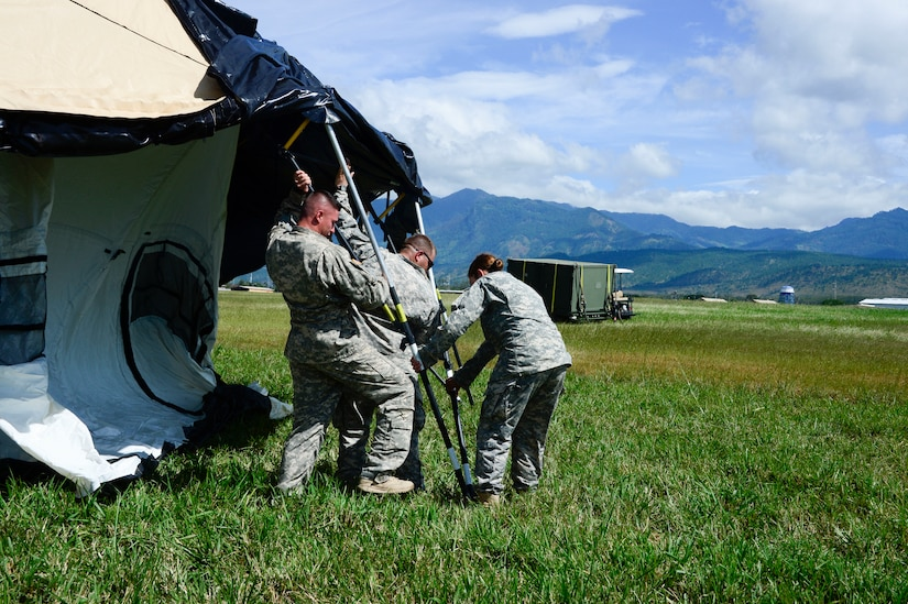 Members from the Joint Task Force-Bravo U. S. Southern Command Situational Assessment Team work together to set up a Deployable Rapid Assembly Shelter during air load and fly-away training on Soto Cano Air Base, Honduras, Nov. 25, 2014.  The members of the S-SAT received training on setting up a Pre-Positioned Expeditionary Assistance Kit to help prepare the team respond efficiently to humanitarian assistance and disaster response situations throughout U.S. Southern Command's area of responsibility.    The training focused on S-SAT familiarization, hands on training and a fly-away event between JTF-Bravo S-SAT personnel, Army Forces Battalion, and 1-228th Aviation Regiment in preparation for an upcoming exercise. (U.S. Air Force photo/Tech. Sgt. Heather Redman)