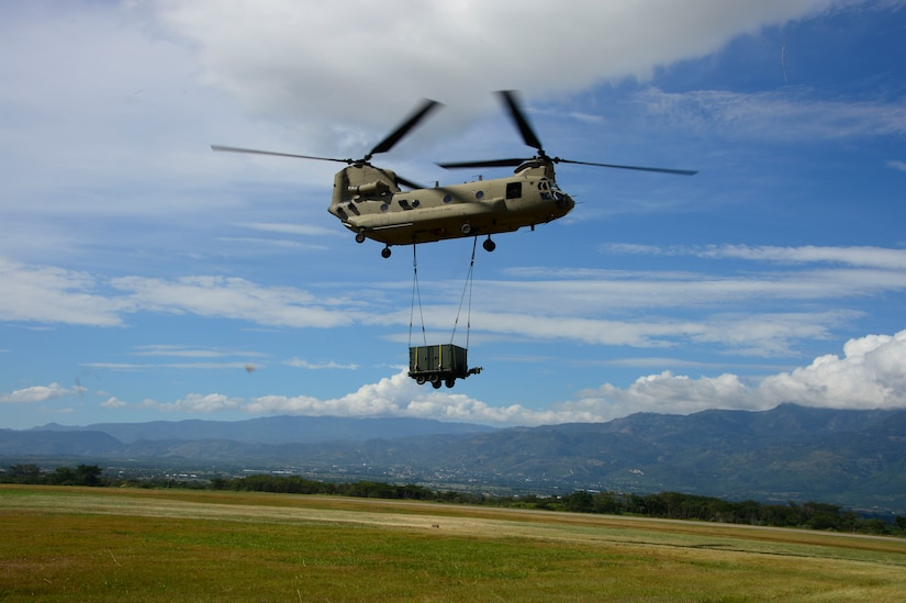 A CH-47 Chinook flies a container to the Warrior Ramp during air load and fly-away training on Soto Cano Air Base, Honduras, Nov. 25, 2014.  The cargo was delivered to the U. S. Southern Command Situational Assessment Team at the Warrior Ramp for employment in the day's training event.  During the training members of the S-SAT received training on setting a Pre-Positioned Expeditionary Assistance Kit to help prepare the team respond efficiently to humanitarian assistance and disaster response situations throughout U.S. Southern Command's area of responsibility.  The training focused on S-SAT familiarization, hands on training and a fly-away event between JTF-Bravo S-SAT personnel, Army Forces Battalion, and 1-228th Aviation Regiment in preparation for an upcoming exercise.  (U.S. Air Force photo/Tech. Sgt. Heather Redman)