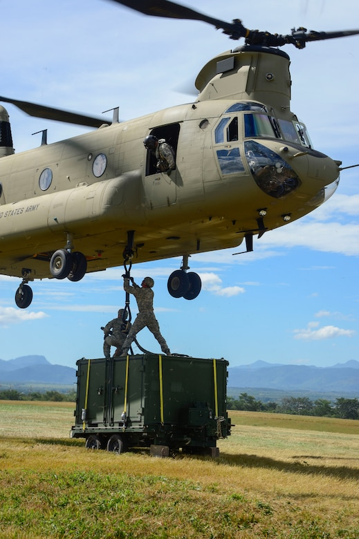 U.S. Army Spcs. Jack Wood and David Swain, assigned to the Army Forces Battalion, attach a container to a CH-47 Chinook during air load and fly-away training on Soto Cano Air Base, Honduras, Nov. 25, 2014.  The cargo was delivered to the U. S. Southern Command Situational Assessment Team at the Warrior Ramp for employment in the day's training event.  During the training members of the S-SAT received training on setting up a Pre-Positioned Expeditionary Assistance Kit to help prepare the team respond efficiently to humanitarian assistance and disaster response situations throughout U.S. Southern Command's area of responsibility.  The training focused on S-SAT familiarization, hands on training and a fly-away event between JTF-Bravo S-SAT personnel, Army Forces Battalion, and 1-228th Aviation Regiment in preparation for an upcoming exercise.  (U.S. Air Force photo/Tech. Sgt. Heather Redman)