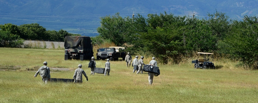 Members from the Joint Task Force-Bravo U. S. Southern Command Situational Assessment Team move equipment from a CH-47 Chinook landing zone at the Warrior Ramp during air load and fly-away training on Soto Cano Air Base, Honduras, Nov. 25, 2014.  The members of the S-SAT received training on setting up a Pre-Positioned Expeditionary Assistance Kit to help prepare the team respond efficiently to humanitarian assistance and disaster response situations throughout U.S. Southern Command's area of responsibility.  The PEAK is designed to provide sustainable, essential services in the first 72 hours after a disaster event.  The training focused on S-SAT familiarization, hands on training and a fly-away event between JTF-Bravo S-SAT personnel, Army Forces Battalion, and 1-228th Aviation Regiment in preparation for an upcoming exercise.  (U.S. Air Force photo/Tech. Sgt. Heather Redman)