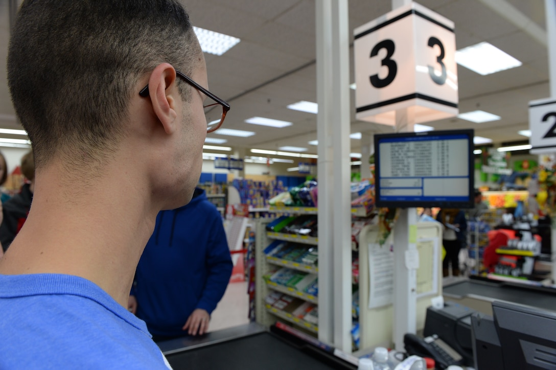 U.S. Air Force Senior Airman Andres Gomez, a 52nd Aerospace Medical Squadron bio-environmental engineering technician, watches the total price of his cart calculate on a screen during the Commissary Sweep Nov. 20, 2014, at the base commissary. The Commissary Sweep pitted five contestants against each other during to compete for a $150 gift card and a cart full of groceries. (U.S. Air Force photo by Airman 1st Class Dylan Nuckolls/Released)