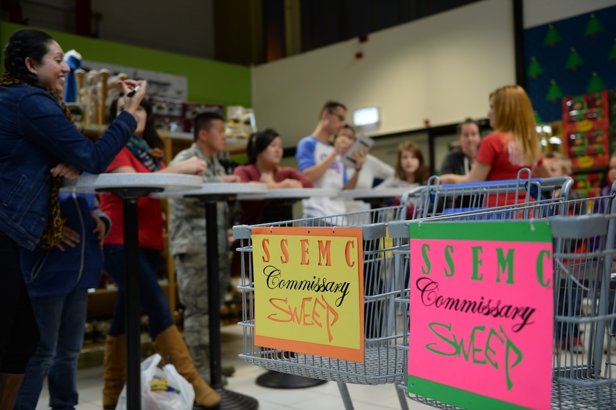 Participants compete during the Commissary Sweep Nov. 20, 2014, at the base commissary. Participants guessed the price of baskets filled with items to earn more money to spend in the final shopping portion of the competition.  (U.S. Air Force photo by Airman 1st Class Dylan Nuckolls/Released)