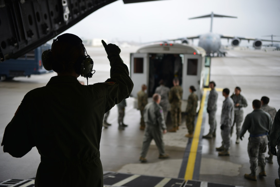 Volunteers and members from the Contingency Aeromedical Staging Facility get the thumbs up to start loading patients on the aircraft on Ramstein Air Base, Germany, Nov. 20, 2014. CASF members wait to get the wheels up call before ending their day. (U.S. Air Force photo/Senior Airman Hailey Haux)