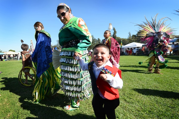 Angelina Alvarez, a Pascua Yaqui tribe member and daughter of a Vietnam veteran, wears jingle dress regalia as she and her 2-year-old son Pedro participate in the Native American Veterans Association's annual Veterans Appreciation and Heritage Day Pow Wow in South Gate, Calif., Nov. 8, 2014. Alvarez's father, a Navy Vietnam veteran and member of SEAL Team 2, received three Purple Hearts, the Navy Cross, and the Silver and Bronze stars. DoD photo by Marvin Lynchard