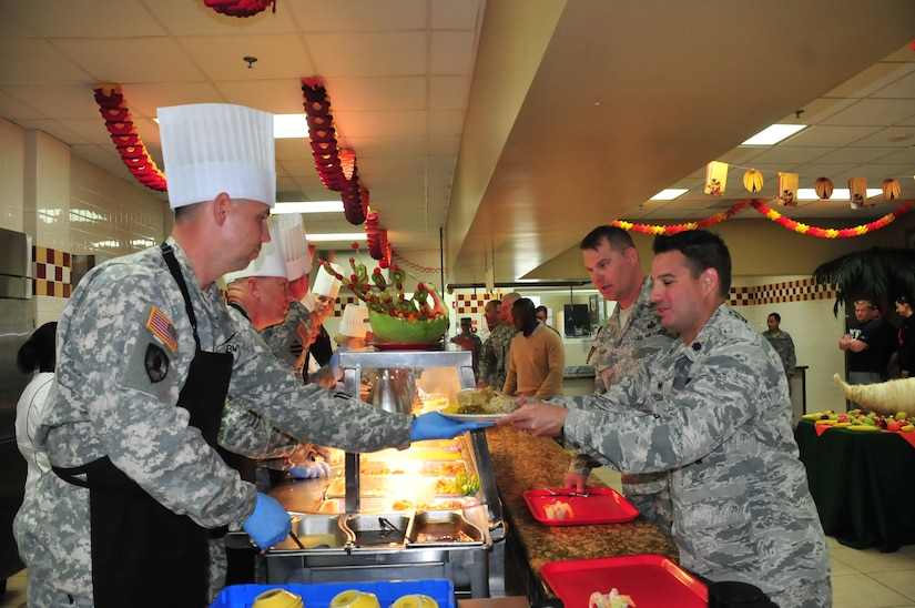U.S. Army Col. Rollie Miller, Army Support Activity commander, serves a plate of Thanksgiving lunch to a service member of Joint Task Force-Bravo at the Soto Cano Air Base dining facility, Nov. 27, 2014.   JTF-Bravo members were treated to a large Thanksgiving Day meal in celebration of the holiday.  Southern Command senior leaders, as well as leaders from JTF-Bravo, ASA, Army Forces Battalion, Joint Security Forces, 612th Air Base Squadron, 1-228th Aviation Regiment, and Medical Element served the members of the Task Force.  (U.S. Air Force photo by Capt. Connie Dillon)