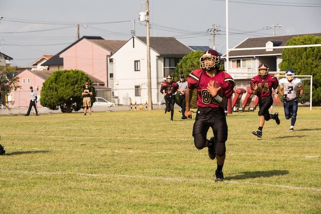 Desmond Moore, Samurai wide receiver and linebacker, runs the ball down the field during Matthew C. Perry High School's first home game of the season against Sotuku High School, Sept. 27, 2014, aboard Marine Corps Air Station Iwakuni, Japan. After beating the Sotuku Fighting Ducks, the Samurai are 3-0 for the season.