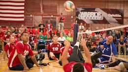 Eric Rodriguez [bottom right], from the Marine Corps volleyball team, tips the ball to teammate Jorge Salazar [middle left] during the Marine Corps vs Air Force volleyball game at the 2014 Warrior Games in Colorado Springs, Colo., Sept. 29. The Marines won the first out of three matches with a final of 25-23.