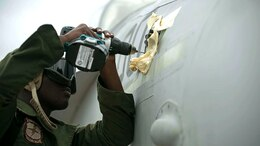 Cpl. Michael P. Hinds, from Queens, N.Y., works on an FA-18 Hornet Sept. 29 during Forager Fury III on Andersen Air Force Base. He is doing routine maintenance to ensure the safety of the pilot. Hinds is an airframes mechanic with Marine All Weather Fighter Attack Squadron 242, Marine Aircraft Group 12, 1st Marine Aircraft Wing, III Marine Expeditionary Force. (U.S. Marine Corps photo by Lance Cpl. Tyler Ngiraswei/ Released)