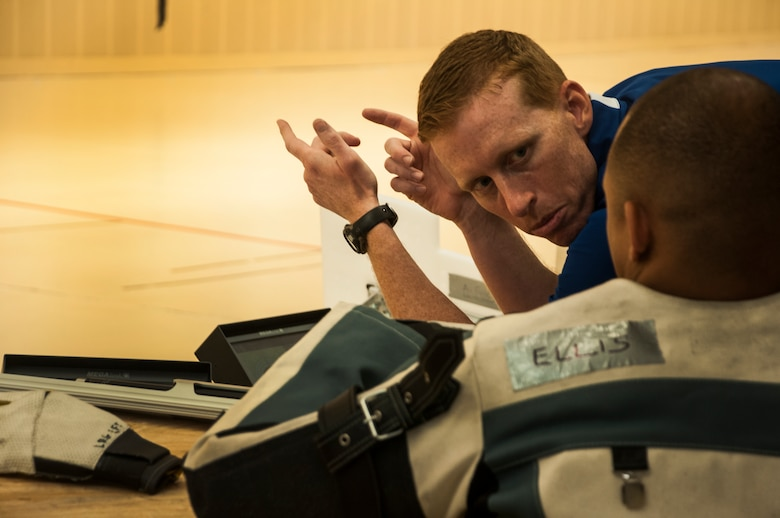 Coach Todd Benson talks to Jason Ellis, Air Force Warrior Games shooting team athlete, regarding his shooting techniques during practice Sept. 26, 2014, at the U.S. Olympic Training Center in Colorado Springs, Colo., prior to the 2014 Warrior Games. More than 200 wounded, ill and injured service members and veterans are currently participating in the games. (U.S. Air Force photo/Staff Sgt. Julius Delos Reyes)