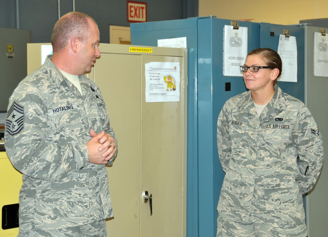 Command Chief Master Sgt. of the Air National Guard James Hotaling coins Airman 1st Class Jennatte Berger of the 109th Maintenance Squadron during a visit to Stratton Air National Guard Base, New York, on Sept. 30, 2014. Berger was recognized by her leadership for being a stand out Airman. Hotaling visited Airmen throughout the base and also held an enlisted town hall meeting. He was at the base in preparation for an upcoming trip to Antarctica with the 109th Airlift Wing in support of Operation Deep Freeze. This will be his first trip to the ice. (U.S. Air National Guard photo by Tech. Sgt. Catharine Schmidt/Released)
