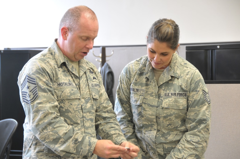 Command Chief Master Sgt. of the Air National Guard James Hotaling coins Tech. Sgt. Brittany Rinaldi of the 109th Force Support Squadron during a visit to Stratton Air National Guard Base, New York, on Sept. 30, 2014. Rinaldi was recognized by her leadership for being a stand out Airman. Hotaling visited Airmen throughout the base and also held an enlisted town hall meeting. He was at the base in preparation for an upcoming trip to Antarctica with the 109th Airlift Wing in support of Operation Deep Freeze. This will be his first trip to the ice. (U.S. Air National Guard photo by Tech. Sgt. Catharine Schmidt/Released)