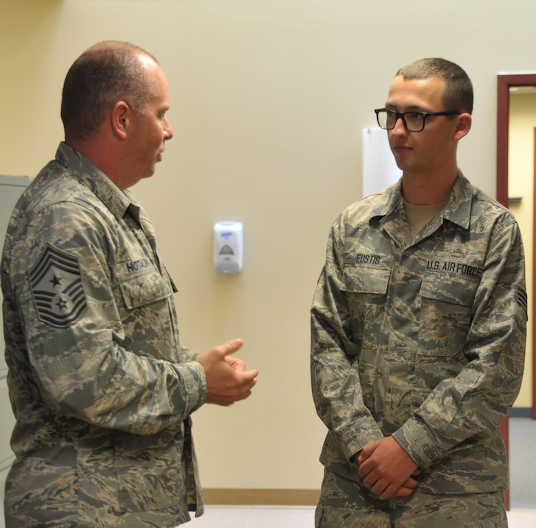 Command Chief Master Sgt. of the Air National Guard James Hotaling coins Senior Airman Collin Eustis of the 109th Communications Flight during a visit to Stratton Air National Guard Base, New York, on Sept. 30, 2014. Eustis was recognized by his leadership for being a stand out Airman. Hotaling visited Airmen throughout the base and also held an enlisted town hall meeting. He was at the base in preparation for an upcoming trip to Antarctica with the 109th Airlift Wing in support of Operation Deep Freeze. This will be his first trip to the ice. (U.S. Air National Guard photo by Tech. Sgt. Catharine Schmidt/Released)