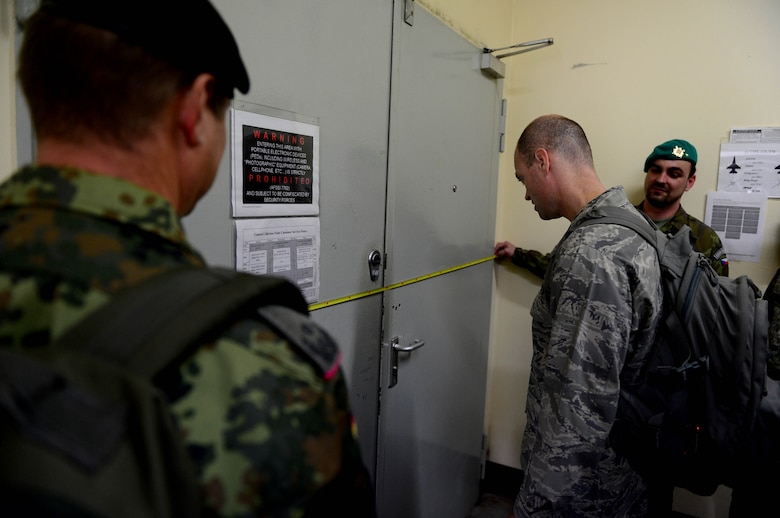 Inspectors from the Conventional Armed Forces in Europe treaty verification team measure an entrance door during an exercise at Spangdahlem Air Base, Germany, Sept. 29, 2014. Inspectors ensure treaty compliance by inspecting random buildings for excessive amounts of warfighting equipment. Inspectors maintain full access to any building with an entrance of two meters or greater in width. (U.S. Air Force photo by Airman 1st Class Kyle Gese/Released)