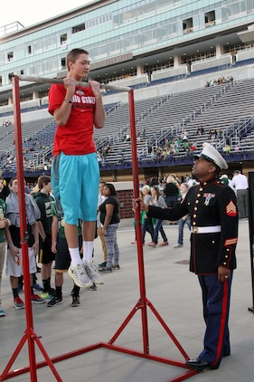 U.S. Marine Corps Sgt.  Ryan Johnson, recruiter at Recruiting Sub-Station Akron and Gary, Indiana, native, steadily holds the pull-up bar for a participant of the pull-up challenge during the Great American Rivalry Series Game featuring St. Vincent St. Mary versus Archbishop Hoban at University of Akron's InfoCision Stadium, Sept. 26, 2014.  The pull-up challenge gave fans the chance to earn points in an effort to win the Pull-up Challenge Spirit Award for their respective school. Archbishop Hoban won the challenge, surpassing St. Vincent St. Mary fans by over 100 pull-ups (U.S. Marine Corps photo by Sgt. T.M. Stewman/Released)