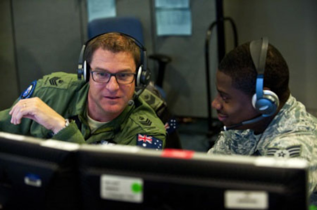 Royal Australian Air Force Flight Sgt. Sean Bedford (left), and Senior Airman Frederick Riggans-Huguley analyze air missile defense systems inside the Combined Air and Space Operations Center-Nellis during Red Flag 14-1 Feb. 5, 2014, at Nellis Air Force Base, Nev. Bedford is a space duty technician with the Australian Space Operations Centre in New Norcia, Australia, and Riggins-Huguley is a space duty technician with the 603rd Air and Space Operations Center at Ramstein Air Base, Germany. Space duty technicians direct air missile ballistic warnings and provide communication to combat search and rescue teams. (U.S. Air Force photo/Senior Airman Brett Clashman)