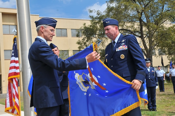 Lt. Gen. Robert Otto, Headquarters Air Force deputy chief of staff, intelligence, surveillance and reconnaissance, left, and Maj. Gen. John Shanahan furl the Air Force ISR Agency flag. Shanahan relinquished command of the agency and assumed command of 25th Air Force during the organization's re-designation ceremony Sept. 29, 2014, on Joint Base San Antonio - Lackland's Security Hill. (U.S. Air Force photo/William Belcher)