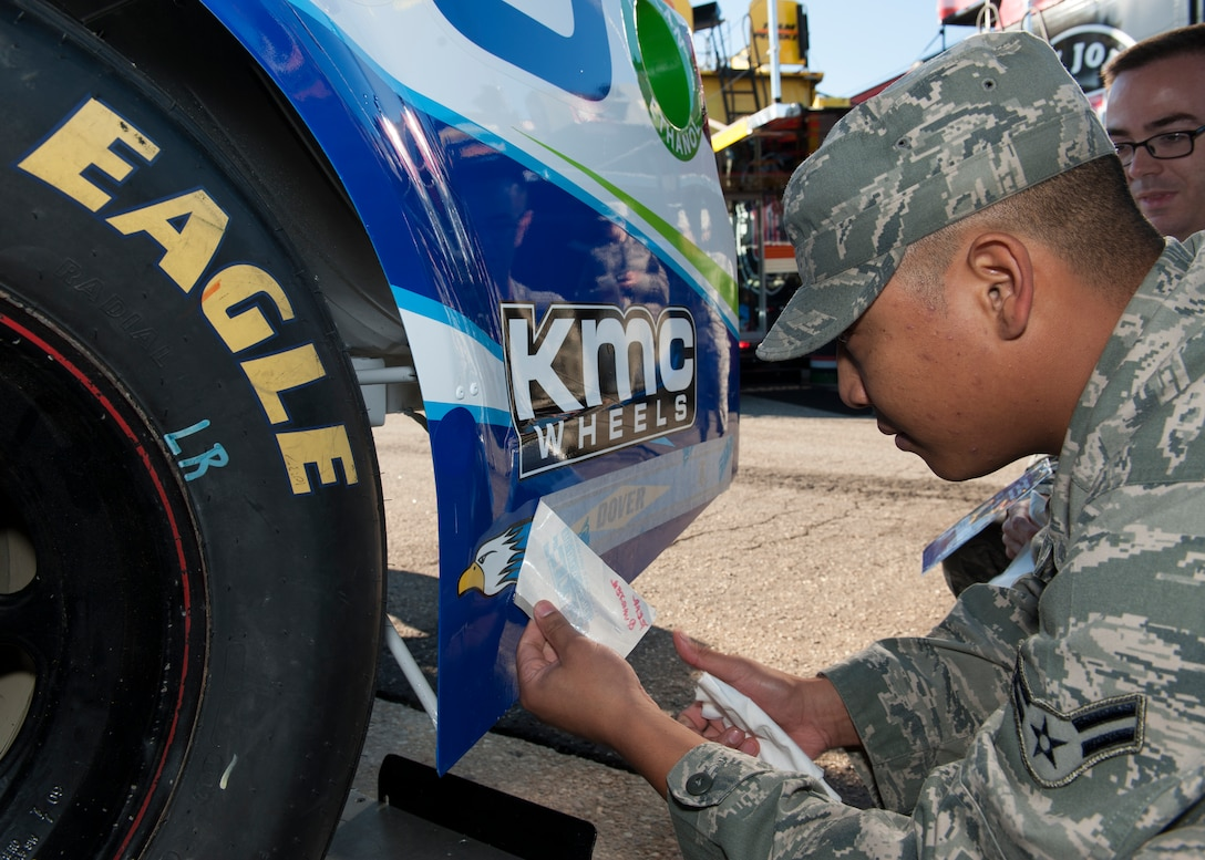 Airman 1st Class Loren Genao applies a Dover Air Force Base tail flash decal to the Germain Racing No. 13 GEICO Chevy SS Sept. 26, 2014, at Dover International Speedway in Dover, Del. This tail flash and two others were placed on the car to thank the Airmen at Dover AFB, Delaware for their service. Genao is an aircraft structural maintainer with the 436th Maintenance Squadron. (U.S. Air Force photo/Airman 1st Class Zachary Cacicia)