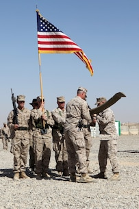 Lieutenant Col. Seth Yost, right, commanding officer, 1st Battalion, 7th Marines, and 1st Sgt. Jordan Freeland, center, Charley Company first sergeant, case the battalion's battle colors during a transfer of authority ceremony aboard Tactical Base Dwyer, Afghanistan, Oct. 1, 2014. The ceremony signified the battalion's transfer of authority of the base and their area of responsibility to 3rd Squadron, 3rd Cavalry Regiment, a U.S. Army command based out of Fort Hood, Texas. The ceremony also meant the end of combat operations for 7th Marines – a regiment which has been actively supporting Operation Enduring Freedom for several years.