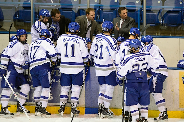 Falcon Ice Hockey head coach Frank Serratore  (right) talks to his team during a match at the Cadet Ice Arena. Serratore said the competitive athlete understands the meaning of leadership and the attributes they gain in competition -- service before self, caring for others and leading front the front -- help them effectively manage their other responsibilities. (U.S. Air Force photo/Mike Kaplan)