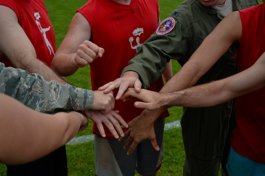 U.S. Air Force Airmen from the 52nd Fighter Wing Staff Agencies place their hands in for a huddle during the Wing Sports Day competition at the base track at Spangdahlem Air Base, Germany, Sept. 29, 2014. The event aimed at boosting esprit de corps among the 52nd FW and offered physical and social competition as part of U.S. Air Forces in Europe's RUFit? Campaign. (U.S. Air Force photo by Staff Sgt. Joe W. McFadden/Released)