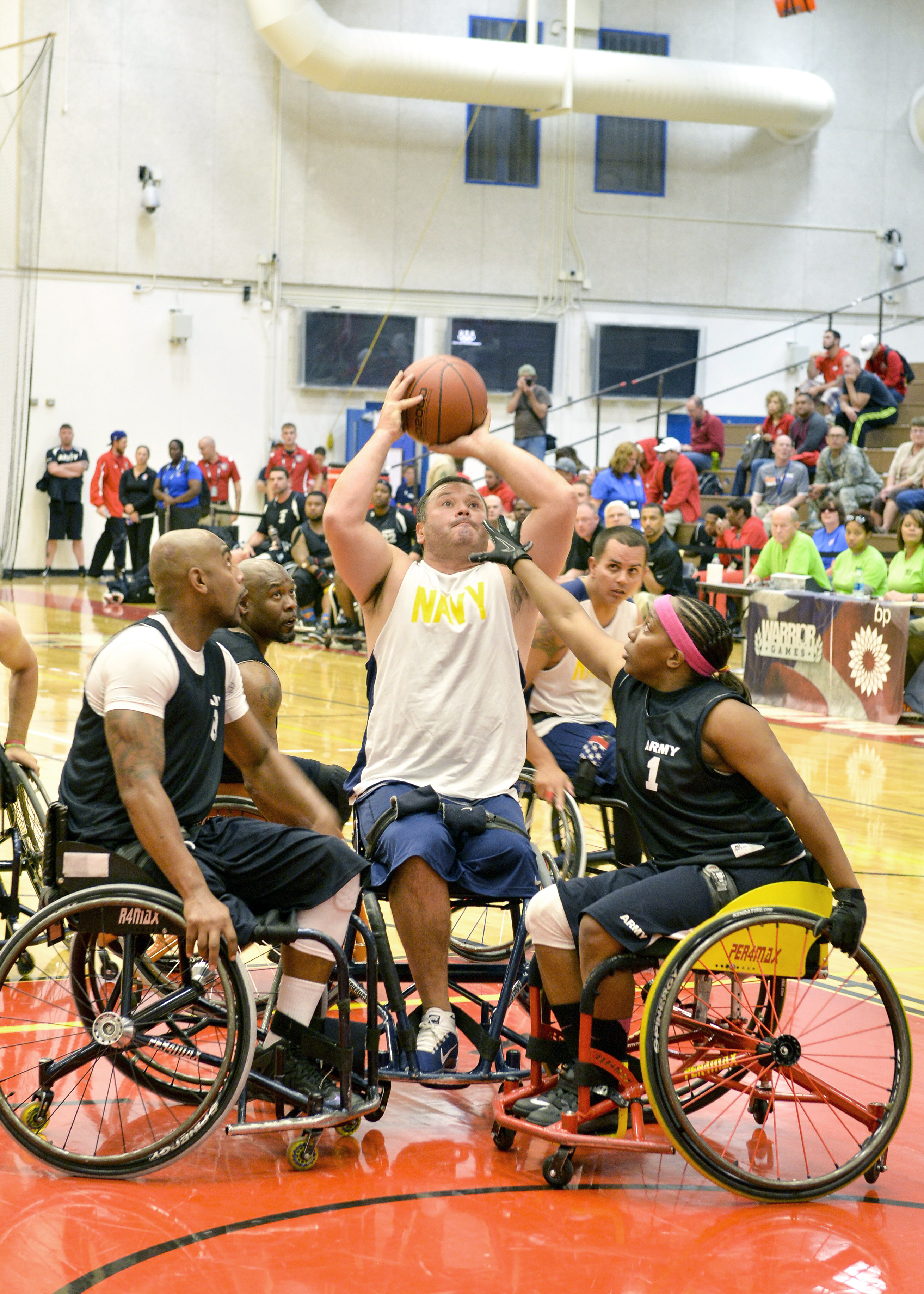 A Navy player is surrounded by Army defenders as he shoots the ball