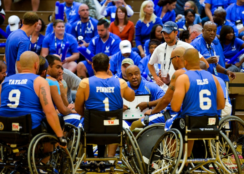Coach Willie Jackson goes over the next play during an Air Force timeout in their game against Navy Sept. 29, 2014, during the 2014 Warrior Games at the U.S. Olympic Training Center in Colorado Springs, Colo. The Air Force lost 38-19. (U.S Air Force photo/Staff Sgt. Devon Suits)