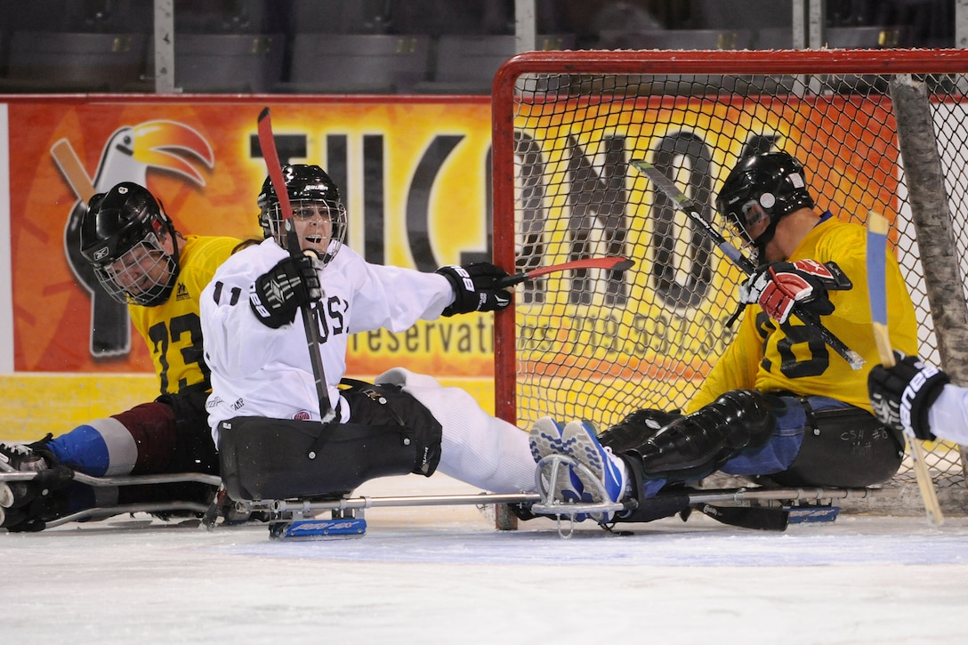 Senior Airman Nikole Sweeney, center, reacts to scoring a goal during a sled hockey game Oct. 2, 2014, at the World Arena in Colorado Springs, Colo. Several athletes competing in the 2014 Warrior Games played sled hockey with local wounded warriors, like Sweeney, as a demonstration before the Los Angeles Kings and Colorado Avalanche professional hockey game. (DOD News photo/EJ Hersom)