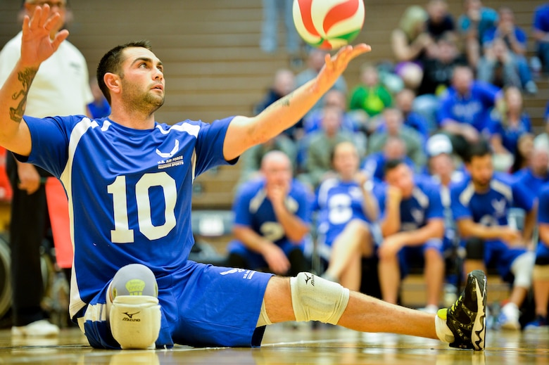 Retired Air Force Staff Sgt. Nicholas Dadgostar serves the ball during the 2014 Warrior Games sitting volleyball bronze medal match between the Air Force and the Army Oct. 1, 2014, at the U.S. Olympic Training Center in Colorado Springs, Colo. The Army beat the Air Force in two sets, 25-20, 25-19. (U.S. Air Force photo/Staff Sgt. Devon Suits)