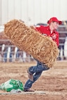 Samantha Jordan hurries to load a hay bale onto a sled pulled by the CGMCG draft horse team of Jenny and Joy Sept. 6 during the farm team race as part of the Draft Horse Competition at the Kansas State Fair in Hutchinson, Kansas. The object of the farm team race was to navigate a course through the arena while stopping twice to collect and drop off hay bales and feed bags.