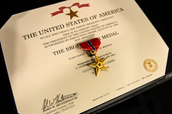 A Bronze Star medal sits on a certificate during a ceremony at the 8th Special Operations Squadron auditorium on Hurlburt Field, Fla., Oct. 2, 2014. This decoration is awarded to a person in any branch of military service who, while serving in any capacity with the United States, distinguish themselves by heroic or meritorious achievement or service. (U.S. Air Force photo/ Airman 1st Class Jeff Parkinson)