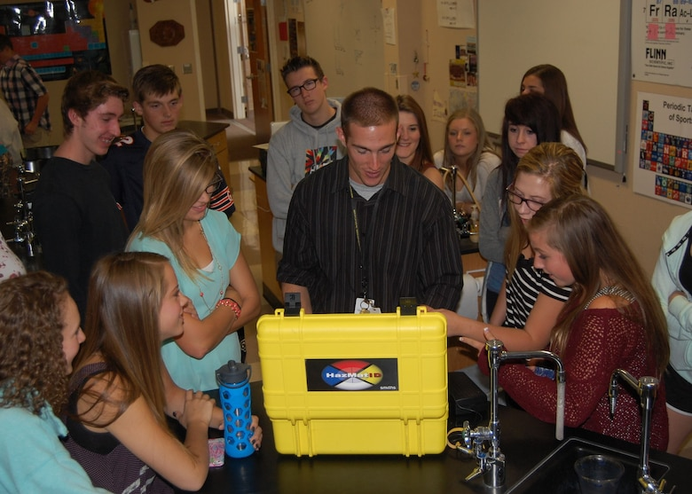 Mr. Bart Blumberg, science teacher at Rock Canyon High School and Traditional Guardsmen with the Colorado Air National Guard, demonstrates how the equipment used by the Emergency Management team is based on the principles the high school students are learning about in chemistry class. Since the science department just learned about light and nuclear chemistry, Master Sgt. Jared Hiles, emergency manager, 140th Wing, brought in some chemical detection equipment that uses infrared spectroscopy and some radiation detectors to reinforce those lessons in Blumberg's classes Sept. 23. (Air National Guard Photo by Capt. Kinder Blacke)