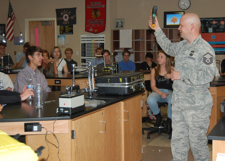 Master Sgt. Jared Hiles, emergency manager, 140th Wing, shares his expertise and equipment with high school students whose science teacher, Mr. Bart Blumberg, is also a Traditional Guardsmen and Staff Sergeant in the 140th Maintenance Squadron. Since the science department just learned about light and nuclear chemistry, Hiles brought in some chemical detection equipment that uses infrared spectroscopy and some radiation detectors to reinforce those lessons in Blumberg's classes. (Air National Guard Photo by Capt. Kinder Blacke)