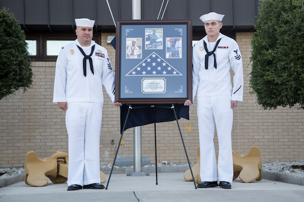 Petty officers unveil a memorial honoring Master-at-Arms 2nd Class Mark Mayo Oct. 3, 2014 at the Naval Technical Training Center Lackland. Mayo died in the line of duty in March 2014 while stationed aboard the USS Mahan (DDG-72) at Norfolk Naval Station, Va.. For his actions that day, Mayo was posthumously awarded the Navy Marine Corps Medal, the second-highest non-combat decoration awarded for heroism. (U.S. Air Force photo by Joshua Rodriguez/Released)