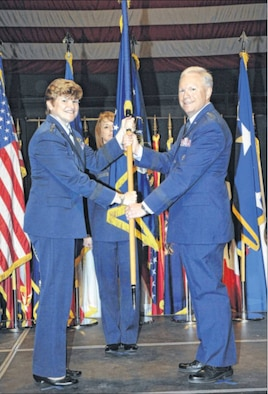Gen. Janet Wolfenbarger, Air Force Materiel Command commander, passes the Air Force Life Cycle Management Center flag to Lt. Gen. John Thompson in a ceremony at the National Museum of the U.S. Air Force on Sept. 26. Thompson officially assumed command of AFLCMC on Oct. 2. (Air Force photo by Al Bright)