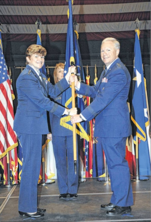 Gen. Janet Wolfenbarger, Air Force Materiel Command commander, passes the Air Force Life Cycle Management Center flag to Lt. Gen. John Thompson in a ceremony at the National Museum of the U.S. Air Force on Sept. 26. Thompson officially assumed command of AFLCMC on Oct. 2. (Air Force photo Al Bright)