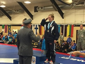 Army Sgt. Whitney Condor salutes the President of CISM Wrestling, Lt Col Marko Korpela (Finland) after receiving her silver medal during the 2014 CISM World Military Wrestling Championship at Joint Base McGuire-Dix-Lakehurst, New Jersey on 3 October 2014.