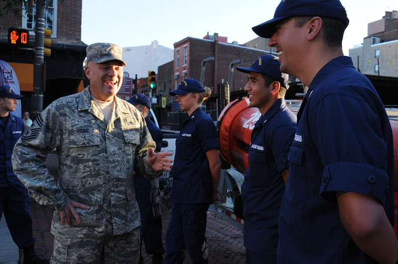 The 111th Attack Wing Command Chief Master Sgt. Paul G. Frisco Jr. talks with local U.S. Coast Guard members during the Fox 29 Salutes the Military Day Sept. 26, 2014, Philadelphia, Pa. The 111th ATKW joined members of each military branch as a show of solidarity during the event. (U.S. Air National Guard photo by Andria J. Allmond/Released)