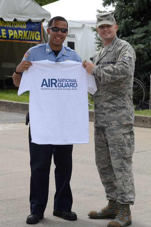 Master Sgt. Kevin Watson, 111th Attack Wing recruiting supervisor at Horsham Air Guard Station, Pa., gives an Air National Guard shirt to a festival employee Aug. 2, during the 30th Annual Musikfest in Bethleham, Pa. The festival composed of diverse music, artisans and vendors boasts thousands of visitors and Pennsylvania residents; the wing's recruiting office chose not to miss the opportunity to connect with a local audience. (U.S. Air National Guard photo by Master Sgt. Chris Botzum/Released)