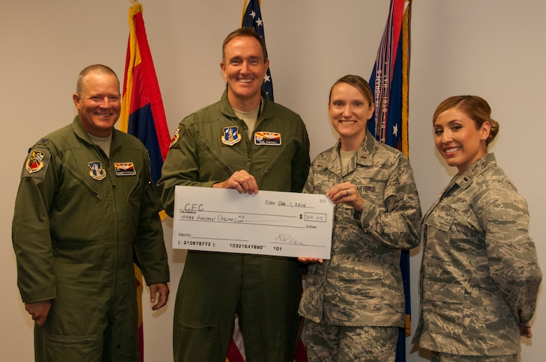 "Col. Phil Purcell, 162nd Wing commander, presents a $300 check to 2014 162nd Wing Combined Federal Campaign coordinators, 1st Lt. Erika Palomino and 2nd Lt. Lacey Roberts. Not to be outdone by the ""boss,"" Vice Wing Commander Kenneth L. Rosson (left) matched Purcell's act of benevolence. (U.S. Air National Guard photo by 2nd Lt. Lacey Roberts)"