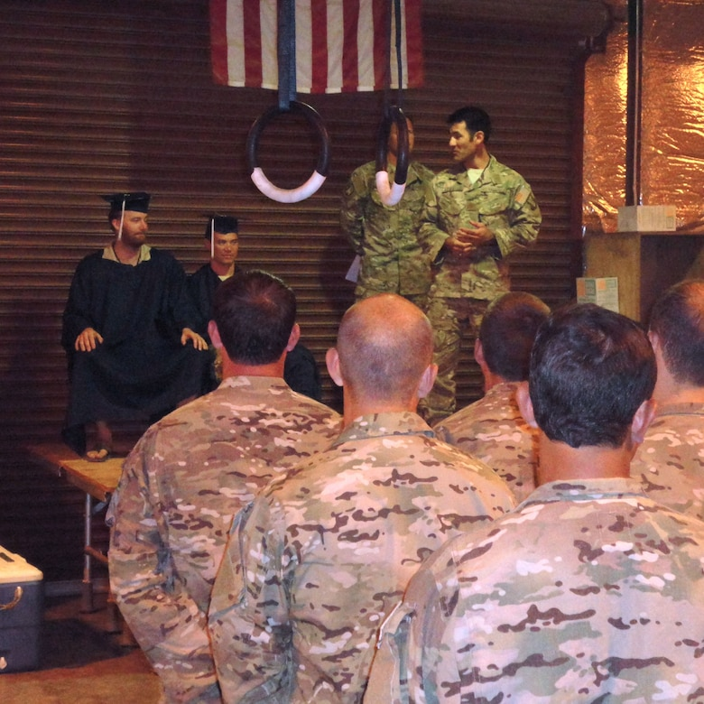 DJIBOUTI, Africa -- Maj. Matthew Komatsu delivers the keynote address to deployed graduates, Master Sgt. Kris Abel and Staff Sgt. Nate Greene, at an intimate graduation ceremony here.