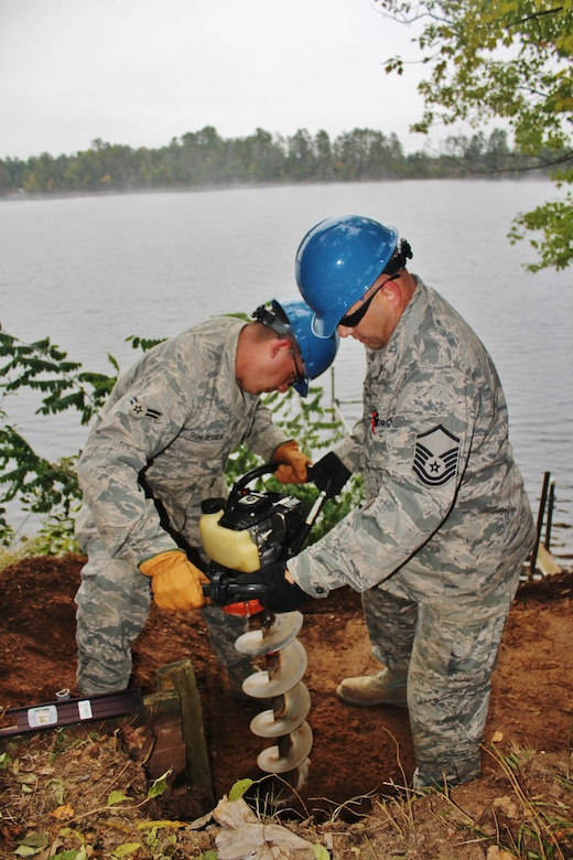 Airman 1st Class Jeremy Schloesser and Master Sgt. Thomas Boissy, both heavy equipment operators with the 128th Civil Engineering Squadron, use a power auger to dig post holes for new stairs and hand railings during the renovation of a cabin at Camp American Legion in Lake Tomahawk, Wis. Sept. 18, 2014. The civil engineering squadron with the 128th Air Refueling Wing, Wisconsin Air National Guard conducted hands-on training while renovating a cabin for Camp American Legion Sept 13-27, 2014. (U.S. Air National Guard photo by Staff Sgt. Josh Garringer/Released)